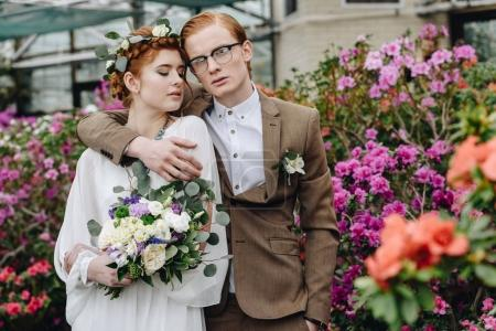 stylish young groom and bride with wedding bouquet standing together in botanical garden