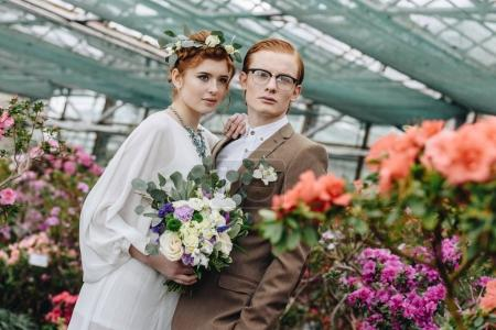 beautiful elegant young red-haired wedding couple standing together between flowers in botanical garden