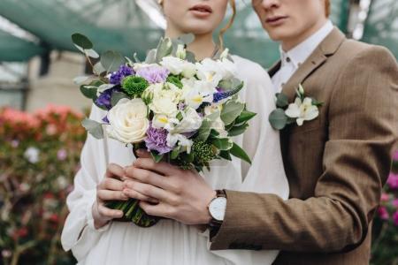 cropped shot of stylish young couple holding beautiful wedding bouquet