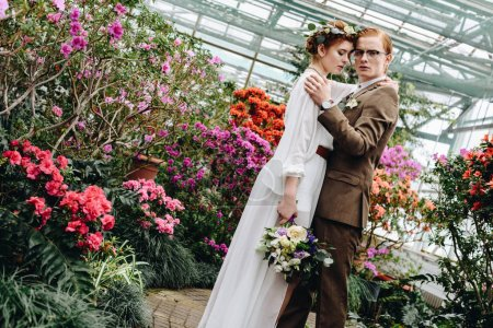 beautiful tender young wedding couple with bouquet standing between flowers in botanical garden