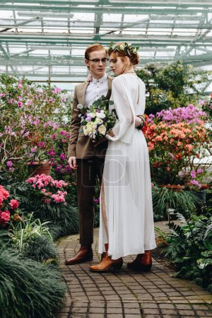 full length view of beautiful young elegant wedding couple standing together between flowers in botanical garden