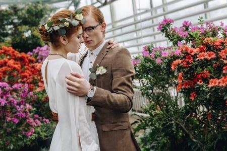 Photo pour Élégant jeune couple rousse de mariage étreignant entre les fleurs dans le jardin botanique - image libre de droit