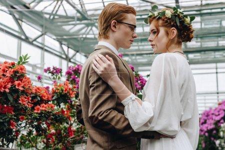Photo pour Beau jeune couple de mariage aux cheveux roux embrassant et se regardant tout en se tenant entre les fleurs dans le jardin botanique - image libre de droit