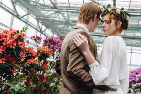 beautiful young elegant wedding couple embracing between flowers in botanical garden