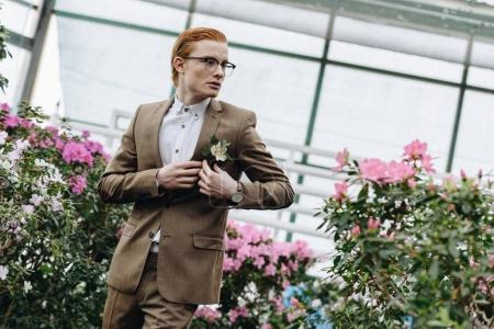 handsome stylish young redhead groom in eyeglasses wearing boutonniere and looking away in botanical garden