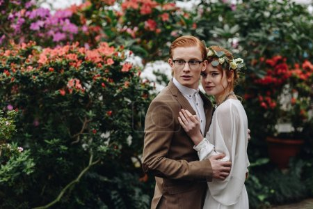 schönes junges elegantes Hochzeitspaar, das zusammen zwischen Blumen steht