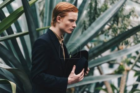 side view of serious young redhead man holding hat and looking away in botanical garden