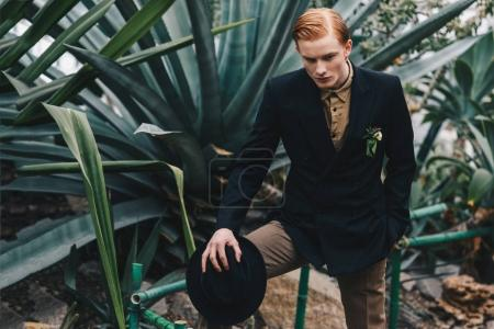handsome stylish young redhead man with boutonniere holding hat and standing in botanical garden