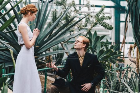 young man standing on knee and making proposal to beautiful redhead girl in botanical garden