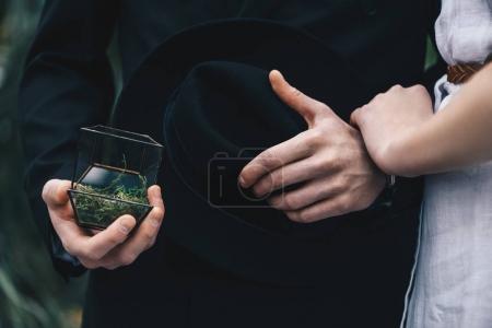 Foto de Foto recortada de pareja joven de pie juntos y hombre con joyero con anillo de compromiso - Imagen libre de derechos