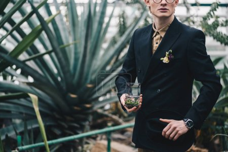 Photo for Cropped shot of stylish young groom holding jewelry box with wedding ring in botanical garden - Royalty Free Image