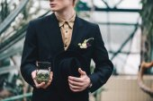 cropped shot of stylish young groom holding jewelry box with wedding ring