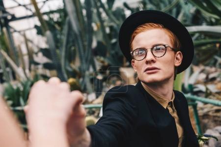 recadrée tir d'élégant jeune homme au chapeau et des lunettes qui fait la proposition à la jeune fille dans le jardin botanique
