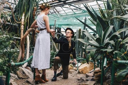 Photo pour Jeune homme avec boîte à bijoux debout sur le genou et tenant la main de belle jeune femme dans le jardin botanique - image libre de droit