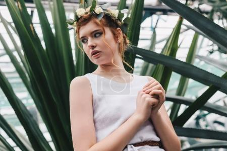 portrait of beautiful elegant red-haired girl in floral wreath looking away
