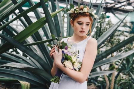 beautiful tender young redhead bride holding wedding bouquet in botanical garden