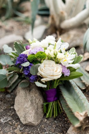 close-up view of tender elegant wedding bouquet with purple ribbon