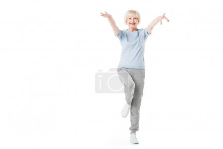 Senior sportswoman standing on one leg isolated on white