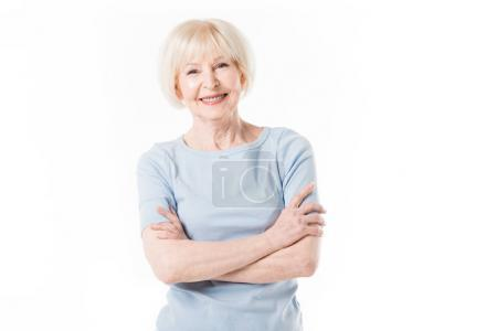 Smiling senior woman standing with crossed arms isolated on white