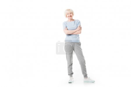 Smiling senior sportswoman standing with crossed arms isolated on white