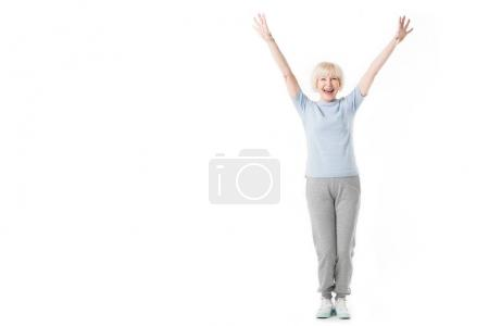 Happy senior sportswoman standing with arms up isolated on white