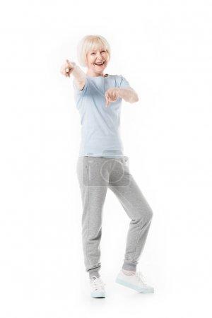 Souriante sportive senior debout et pointant par doigts isolés sur blanc