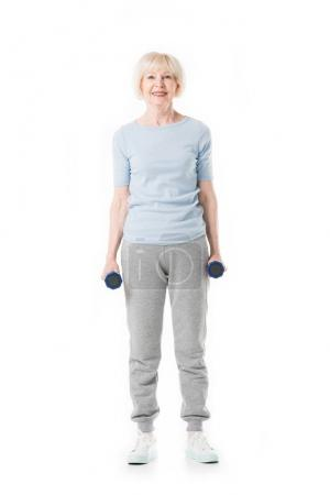 Senior sportswoman standing with dumbbells in hands isolated on white