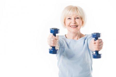 Sportive senior souriante avec des haltères en mains isolés sur blanc