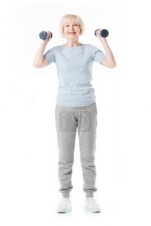 Happy senior sportswoman holding dumbbells in hands isolated on white