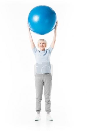 Senior sportswoman with arms up holding fitness ball isolated on white