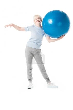Senior sportswoman holding fitness ball in one hand isolated on white