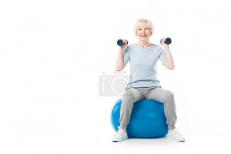 Smiling senior sportswoman with dumbbells sitting on fitness ball isolated on white