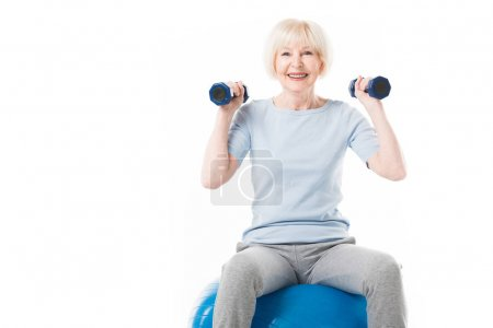 Senior sportswoman with dumbbells sitting on fitness ball isolated on white
