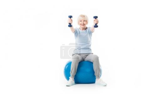 Photo for Smiling senior sportswoman holding dumbbells while sitting on fitness ball isolated on white - Royalty Free Image