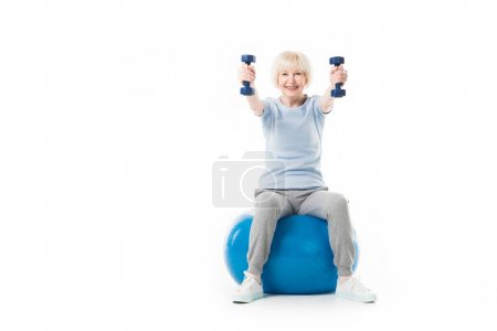 Smiling senior sportswoman holding dumbbells while sitting on fitness ball isolated on white