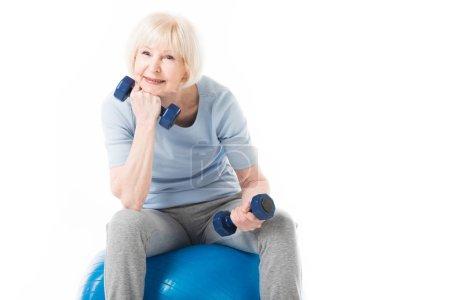 Photo pour Sportive Senior assis sur ballon de fitness avec haltères en mains isolés sur blanc - image libre de droit