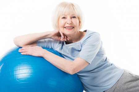 Portrait of smiling senior sportswoman with fitness ball isolated on white