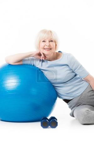 Smiling senior sportswoman with fitness ball and dumbbells isolated on white