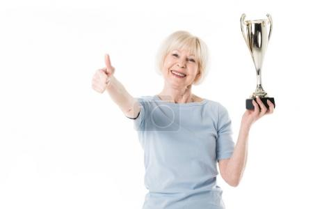 Portrait of smiling senior sportswoman showing thumb up gesture and holding trophy isolated on white