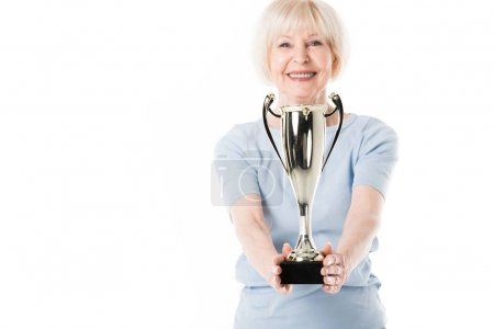 Smiling senior sportswoman holding trophy in hands isolated on white
