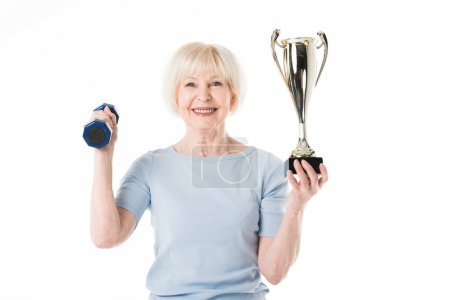 Senior sportswoman with trophy and dumbbell isolated on white