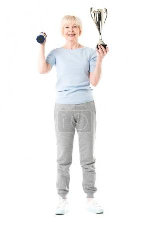 Smiling senior sportswoman with trophy and dumbbell isolated on white