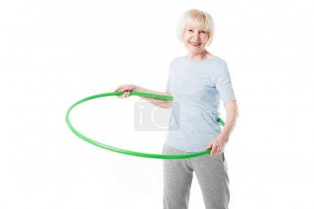 Senior sportswoman doing hula hoop exercise isolated on white