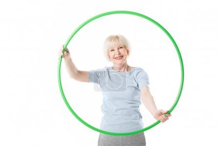 Portrait of senior sportswoman holding hula hoop isolated on white