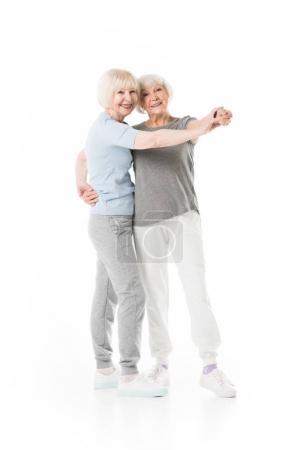 Two senior sportswomen doing exercise isolated on white
