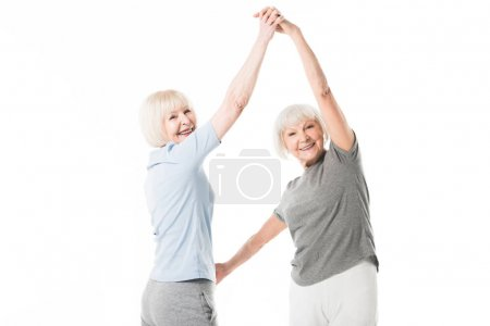 Two smiling senior sportswomen doing exercise isolated on white