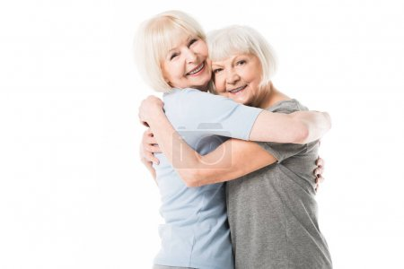 Smiling senior women embracing each other isolated on white