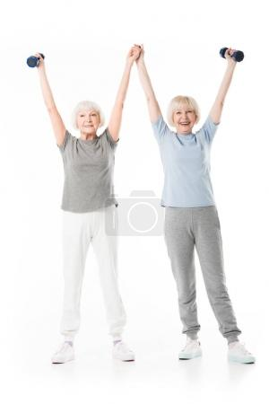 Two senior sportswomen with arms up holding dumbbell isolated on white