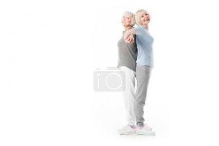Smiling senior sportswomen standing back to back isolated on white