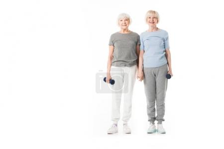 Two senior sportswomen with dumbbell in hand isolated on white